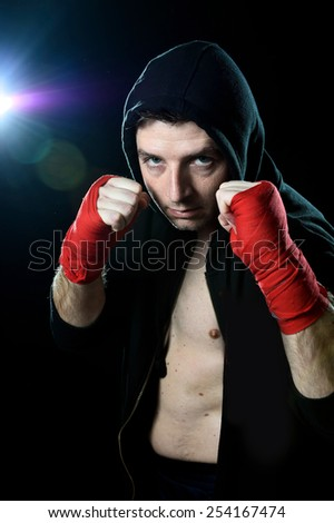 young man in boxing hoodie jumper with hood on head wearing hand and wrist wrapped posing on boxer stance in black background with angry face expression - stock photo