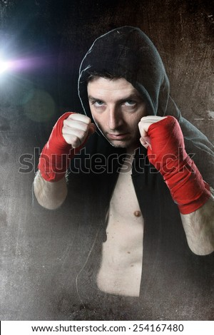 young man in boxing hoodie jumper with hood on head wearing hand and wrist wrapped posing on boxer stance in grunge dirty background with angry face expression - stock photo