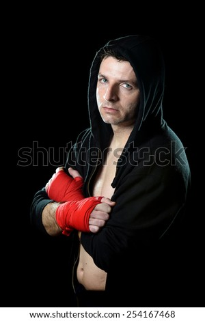 young man in boxing hoodie jumper with hood on head wearing hand and wrist wrapped ready for fighting posing isolated on black grunge dirty background with angry face expression - stock photo