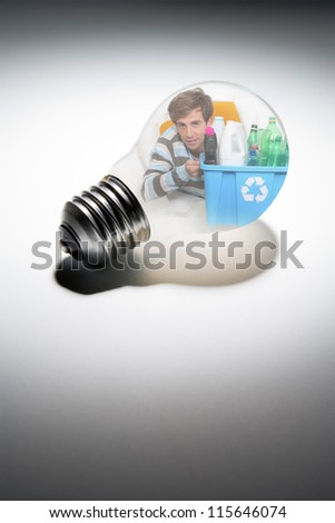 young man in bulb with recycling tub - stock photo