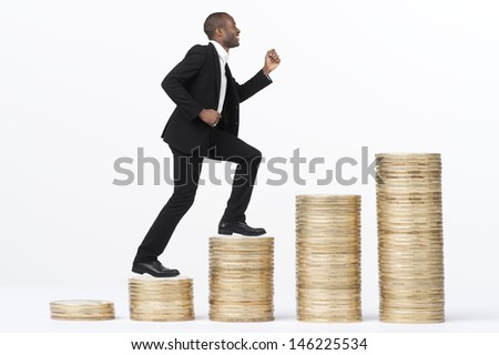 Young man in business attire climbinb giant stacks of money. Shot in studio over white.