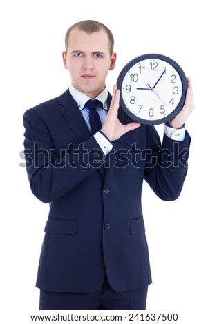 young man in business suit holding office clock isolated on white background