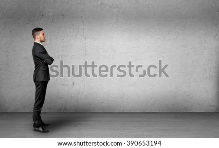 Young man in business suit, standing front of the concrete wall background. Business concept - stock photo