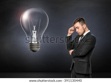 Young man in business suit thinking, on concrete wall background. Broken light bulb. Business concept