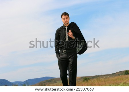 Young man in business suit walking towards the camera. - stock photo