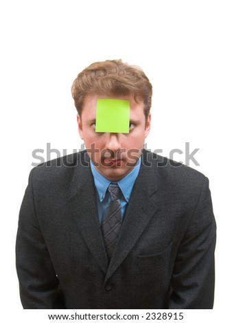 Young man in business suite with a sticky note attached to his forehead bend forward to camera isolated on white - stock photo
