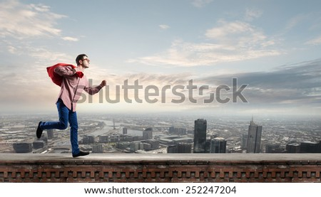 Young man in casual carrying heavy red bag