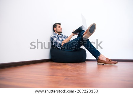 Young man in casual cloth sitting on bag chair and using laptop - stock photo