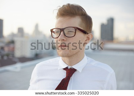 Young man in casual fashion hipster style in glasses and necktie on the rooftop - stock photo