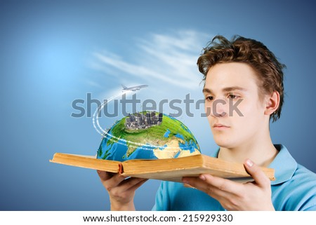 Young man in casual holding opened book with city model. Elements of this image are furnished by NASA