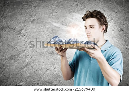 Young man in casual holding opened book with mountain landscape - stock photo