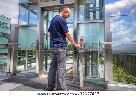 young man in casual pushing the button to call an elevator in-front of a train station - stock photo