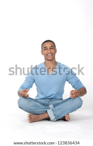 Young man in casual sitting in the lotus position over white background