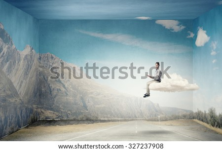 Young man in casual sitting on cloud with book in hands - stock photo