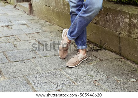 Young man in casual summer clothes in light beige suede leather shoes with laces near the parapet in the park. Men's fashion, style, fashion trends.