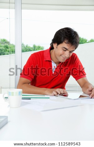 Young man in casual t-shirt using digital tablet while sitting at desk