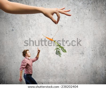 Young man in casual teased by carrot hanging on rope - stock photo