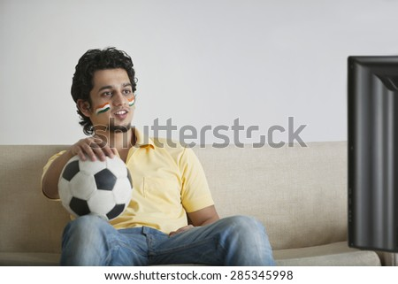 Young man in casuals with face painted watching television while holding soccer ball - stock photo