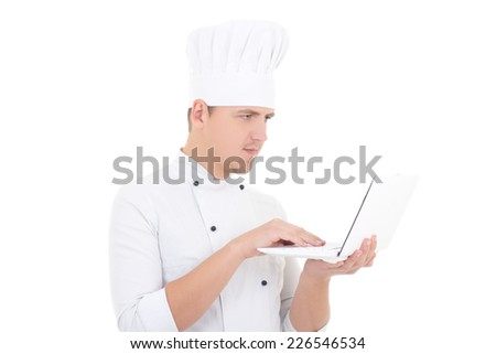 young man in chef uniform with laptop isolated on white background - stock photo