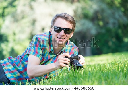 Young man in colorful shirt with digital camera shooting macro on green fresh grass in park