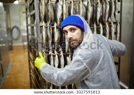 Young man in coveralls and gloves pushing cart with hanging fish and looking at camera