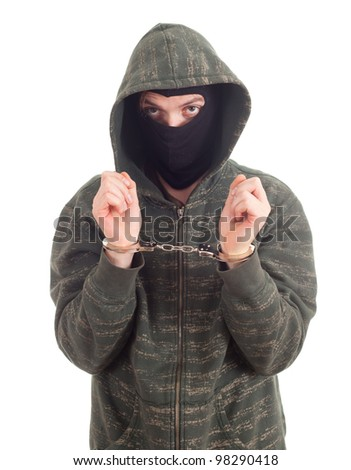 young man in dark sweatshirt and black mask with handcuffed hands - stock photo