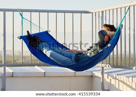 Young man in denim clothes naps in hammock attached to building roof fencing. - stock photo