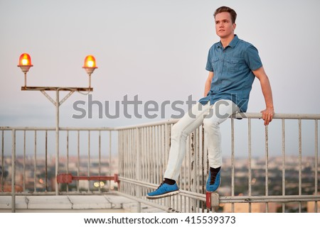 Young man in denim clothes sits on the fencing of the building roof.