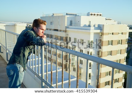 Young man in denim clothes stands on the building roof leaning to the fencing. - stock photo