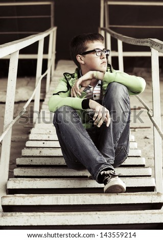 Young man in depression sitting on the steps - stock photo