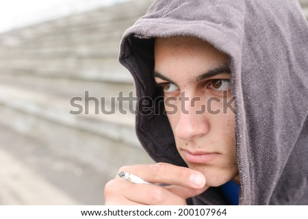 Young man in depression smoking a cigarette on a stadium. Concept of young people with harmful habits - stock photo