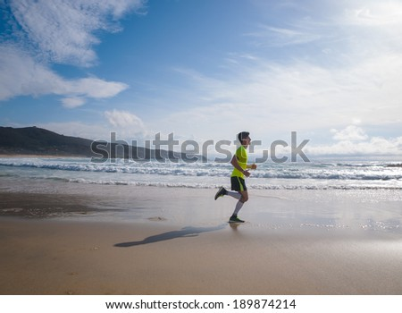 Young Man In Fitness Clothing Running Along Beach outdoors - stock photo