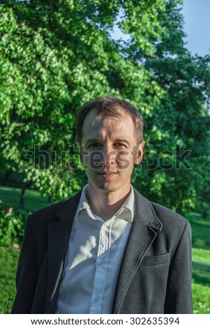 Young man in formal outfit looking seriously in camera, outdoors on the green background. Business man in a green zone or park. An image for topics of finance and business. - stock photo