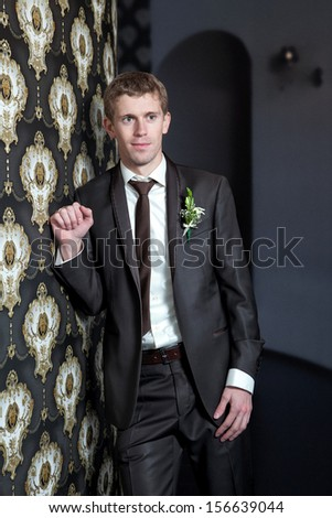 Young man in formal wear leaning against a wall. - stock photo