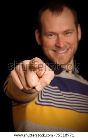 Young man in front of black background pointing at you - stock photo