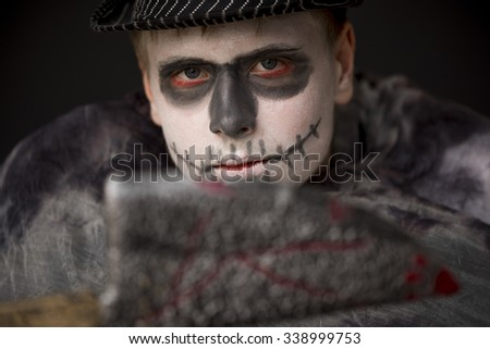 Young man in ghoulish Halloween skull makeup wrapped in dark clothing and hat brandishing a bloodied knife at the camera, focus to his face