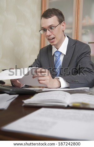 Young man in glasses is looking at paper sheet, open wide his eyes and mouth (shocked)