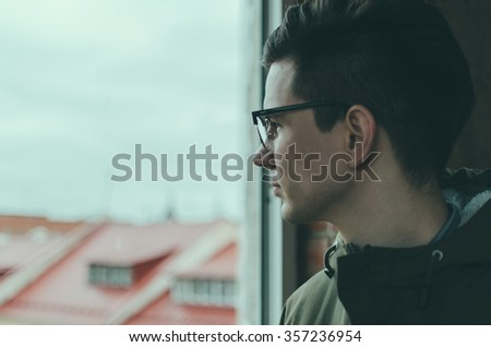 Young man in glasses looking through a window - stock photo