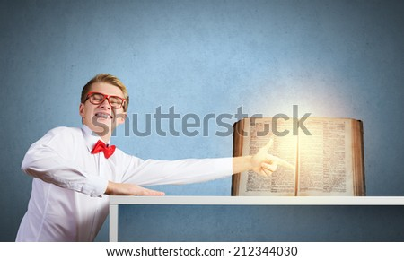 Young man in glasses pointing at opened book - stock photo
