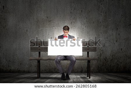 Young man in glasses sitting on bench with white banner - stock photo