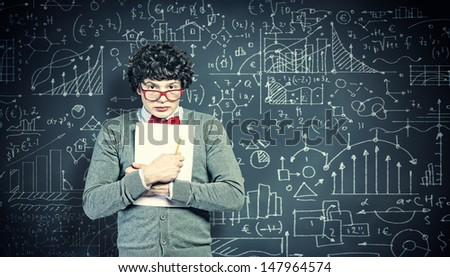 Young man in glasses standing and holding papers against blackboard