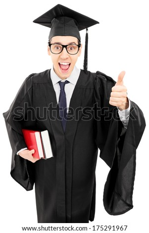 Young man in graduation gown holding books and giving thumb up isolated on white background