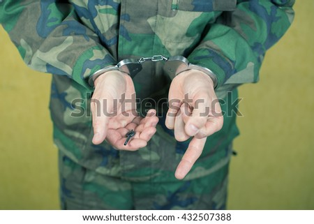 Young man in handcuffs wearing camouflage uniforms in the room. - stock photo
