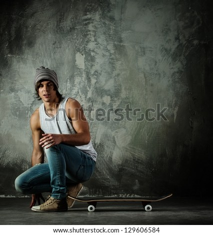 Young man in hat and jeans sitting near skateboard - stock photo