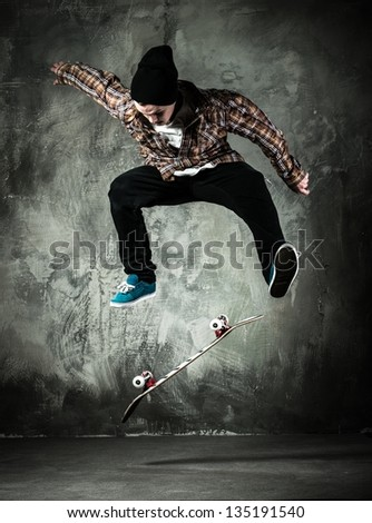 Young man in hat and shirt performing stunt on skateboard - stock photo