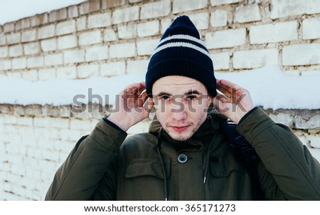 Young man in hat on the brick wall background