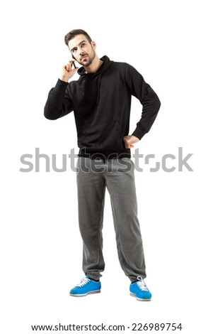 Young man in hood and sweatpants talking on mobile phone.  Full body length isolated over white background. - stock photo