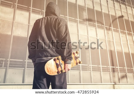 Young man in hood  with skateboard on city town background. Fashion Free Relax Skateboard Trendy Teenager Concept. Youth skateboard subculture.