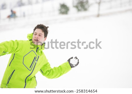 Young man in hooded jacket throwing snowball - stock photo