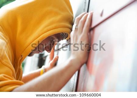 Young man in hooded sweatshirt / jumper facing grunge graffiti wall. Conceptual - stock photo